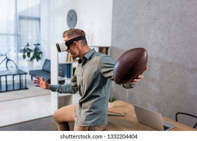 businessman wearing virtual reality headset and holding american football in offcie