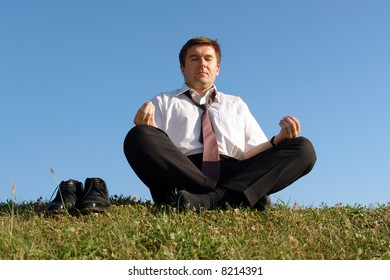 Businessman wearing white shirt and tie meditating on grass with his shoes off over clear blue sky