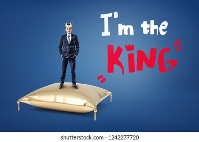 A businessman wears a crown and stands on a golden cushion with the words 'I'm the King' written near him. Born leader. Top management. Business empire.