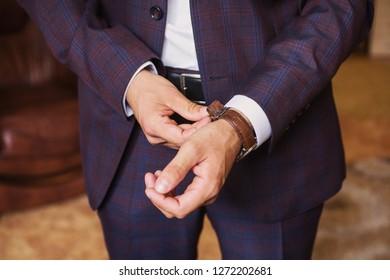 Businessman wears stylish wrist watch. Stylish man in new suit. Adult stylish person