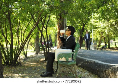 Businessman wears suit and sits on wooden bench in the park drinking coffee relaxing in the park