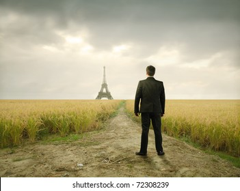Businessman in a wheat field with Eiffel Tower on the background