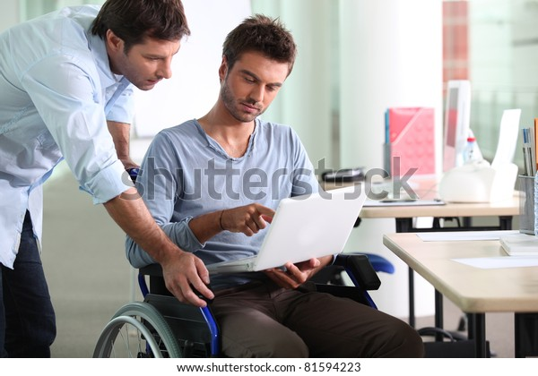 Businessman in wheelchair with laptop computer