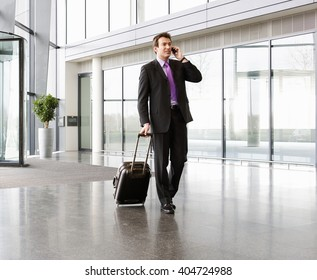 A businessman wheeling a trolley suitcase, talking on a mobile phone