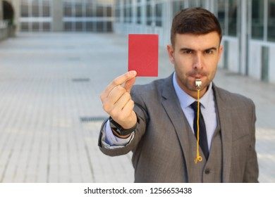 Businessman with whistle and red card