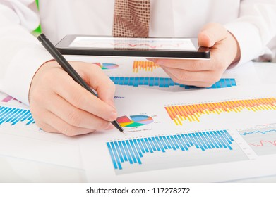 Businessman in white shirt analyzing graphs and charts