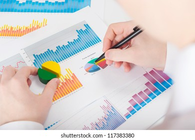 Businessman in white shirt analyzing graphs. Rear view