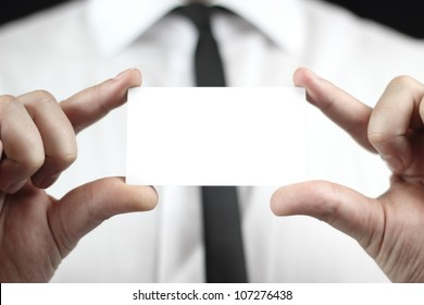 Businessman in white shirt with a black tie, shows business card with copy space