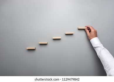 Businessman in white shirt building a graph or ladder of success on grey background.