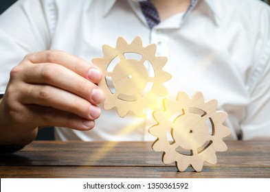 Businessman in white shirt connects two wooden gears. Symbolism of establishing business processes and communication. Increase efficiency and productivity. The best business formula for success.