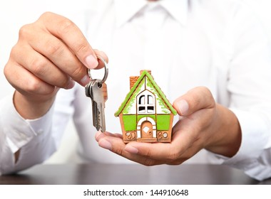 businessman in white shirt holding a small house and apartment keys in hand
