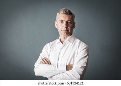 Businessman in white shirt looks at us on gray wall background