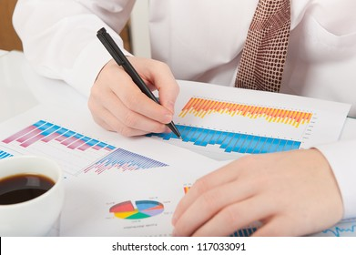 Businessman in white shirt and necktie analyzing graphs