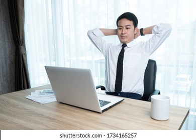 Businessman in white shirt relaxing from his work in his office room.