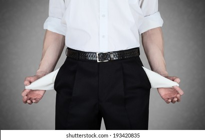 Businessman in white shirt shows empty pockets of his trousers