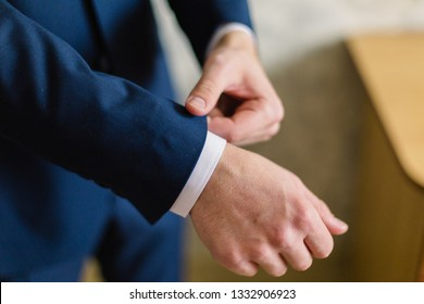 Businessman in a white shirt straightens cuffs, standing at the window in natural light. Man buttons cuff-link on French cuffs sleeves luxury white shirt. Concept successfully bisinesman