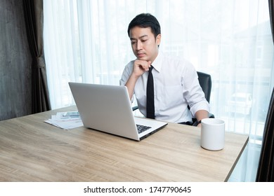 Businessman in white shirt thinking and analyze about his work in his office room.