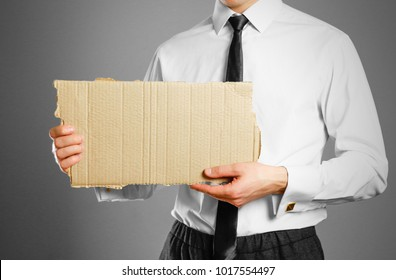 Businessman in white shirt and tie holding a piece of cardboard. Clean empty paper for your text.