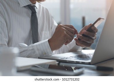 Businessman in white shirt using mobile smart phone and working or browsing internet on laptop computer in modern office with digital tablet, notebook on table near the window, flare light, close up