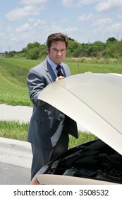 A businessman whose car has broken down, checking under the hood.