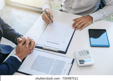 Businessman will be signing a car insurance policy, Agent man is holding the document and waiting for his reply to finish.