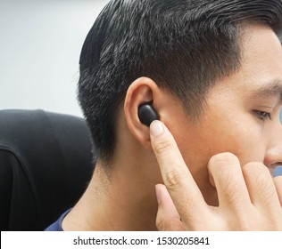 businessman with wireless Bluetooth earphone working with computer in office