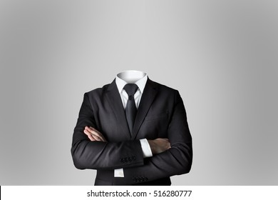 businessman without head crossed arms dark grey background