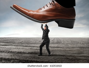 Businessman withstanding a shoe trying to squeeze him