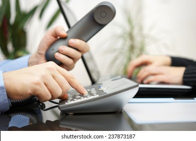 businessman and woman are contacting new clients  over telephone and internet