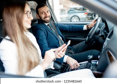 Businessman and woman dressed in the suits talking together while driving a luxury car in the city