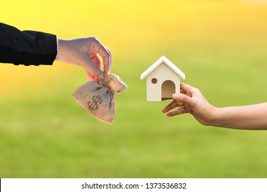 Businessman and woman hand holding a model home and money bag presenting to each other in the public park, Saving money for buy a house or loan for business investment to real estate concept.