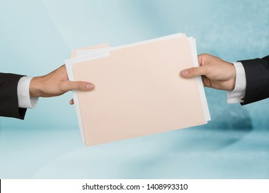 Businessman and woman handing paper file folder