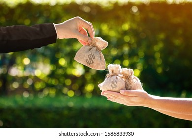 Businessman and a woman hands hold a money bags in the public park for loans to planned investment in the future concept.