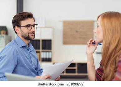 Businessman and woman having a meeting sitting facing each other discussing paperwork with serious expression, focus on the man