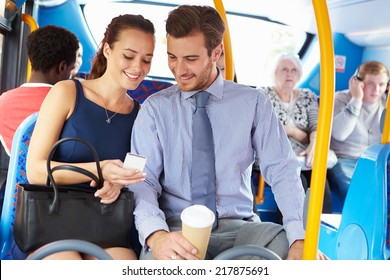 Businessman And Woman Looking At Mobile Phone On Bus