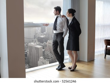 Businessman and woman looking out of a window
