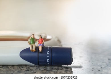 Businessman and woman miniature figure sitting on lancet with Glucose meter for check blood sugar level using as Medicine, diabetes, glycemia, health care and people concept.