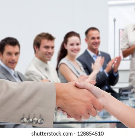 Businessman and woman shaking hands in presentation with business team clapping