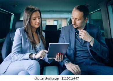Geschäftsmann und Geschäftsfrau, die mit einem VW-Transfer reisen. Geschäftsfrau und Geschäftsmann im Rücksitz des Luxusminivan