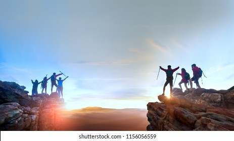 Businessman and women group hike on the peak of  rocks mountain at sunset, success, winner, leader and Teamwork concept .
