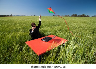 Businessman wondering if his idea will fly.  Man in suit at desk in field flying a kite, representing his latest idea.