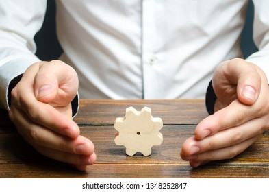 Businessman and wooden gear. Establishing business processes and communications. Development of business relations and cooperation. Efficiency increase and cost reduction. Reduced bureaucratic burden