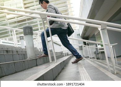 Businessman with work bag going up the stairs in a hurry, Focus on legs and feet. Climbing corporate ladder or work success concept.