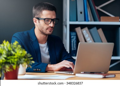 Businessman at work. Concentrated young man working on laptop while sitting at his working place in office