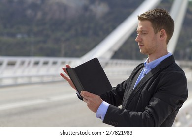 Businessman At Work With His Touch pad On The Bridge