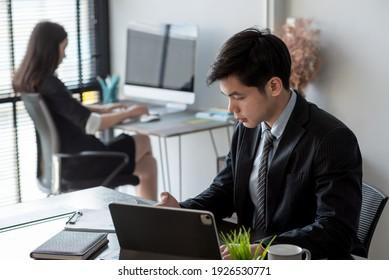 ิAsian businessman work in the office using tablet and mobile phone.