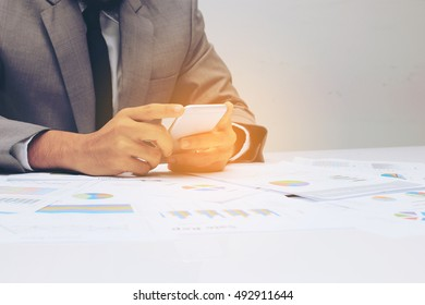Businessman work on table with using smart phone in hand with graph and chart sheet paper document report background at early sunlight. at the office
