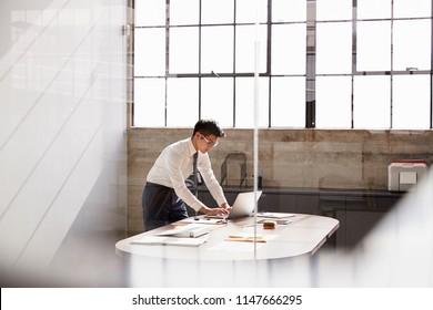 Businessman working alone in a office, seen through window