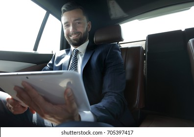 businessman working in the back seat of a car and using a tablet