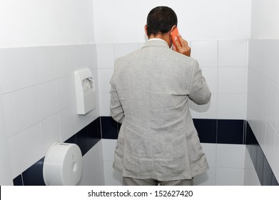 Businessman working in the bathroom with his smartphone as a concept to work anywhere